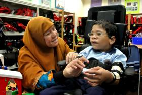 Madam Faridah Thamby calming her son, Fahmi, down by gently touching his arm and singing to him.