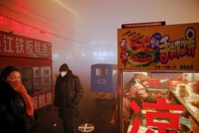 People waiting for street food as heavy smog blankets Shengfang, in Hebei province.