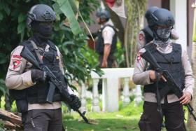 Armed Indonesian police secure a house after a firefight erupted as alleged militants had opened fire at officers in South Tangerang, 25 kilometres (15 miles) outside the capital Jakarta.