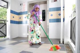 Madam Zulaika sweeping away rainwater that had collected along the common corridor.
