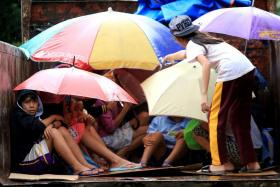 Young residents sit in a truck after the local government implemented preemptive evacuations at Barangay Matnog, Daraga, Albay province on December 25, 2016, due to the approaching typhoon Nock-Ten.