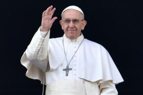 """Pope Francis waves from the balcony of St Peter's basilica during the traditional """"Urbi et Orbi"""" Christmas message to the city and the world, on December 25, 2016 at St Peter's square in Vatican."""