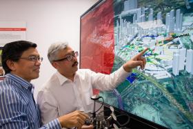 Prof Low Kin Huat (left) and Air Traffic Management Research Institute Deputy Director Mohamed Faisal Mohamed Salleh discussing an air traffic simulation.