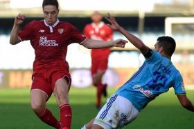 Sevilla's Samir Nasri (L) vies with Celta Vigo's Gustavo Cabral during the Spanish league football on December 11, 2016