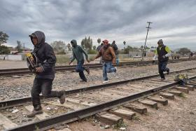 Migrants running to receive food as they attempt to cross the US border.