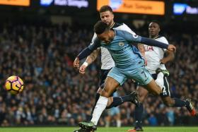 Manchester City's English midfielder Raheem Sterling (in blue) fails to score with this late attempt as Tottenham Hotspur's defender Kyle Walker (partially hidden) appears to push him slightly. The match ended 2-2 at the Etihad Stadium