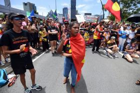 Many people turned up in the aboriginal flag colours to protest against Australia Day being on Jan 26.