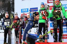 France's Martin Fourcade (centre) leaving the podium during the winners' ceremony as Russian rivals were being presented medals.