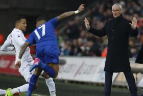 Swansea City's Martin Olsson in action with Leicester City's Danny Simpson while Leicester City manager Claudio Ranieri looks on