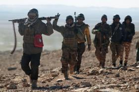 Iraqi forces, supported by the Hashed al-Shaabi (Popular Mobilisation) paramilitaries, advance near the village of Sheikh Younis, south of Mosul