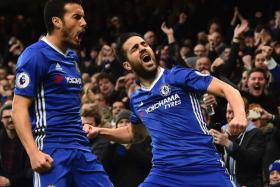Chelsea's Spanish midfielder Cesc Fabregas (R) and Chelsea's Spanish midfielder Pedro (L) celebrate after Fabregas scored the opening goal during the English Premier League football match between Chelsea and Swansea at Stamford Bridge in London on February 25, 2017