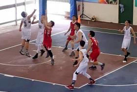 Two Anglican High players (in white) tussling with a Dunman Secondary School player for the ball.