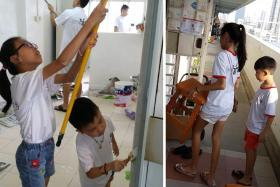Mr Lim's daughter, Reane, 12 and son, Reven, 8, helping to paint a wall in one of the flats visited on their weekly Sunday visits to needy homes in Singapore