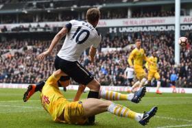 Spurs striker Harry Kane is tackled by Millwall's English defender Jake Cooper