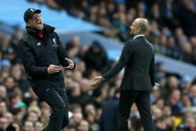 Manchester City's manager Pep Guardiola (R) and Liverpool's manager Juergen Klopp react during their EPL clash