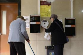 A woman gets toilet paper from a dispenser next to two unused automatic toilet paper dispensers that use facial recognition technology at a public toilet at the Temple of Heaven in Beijing.