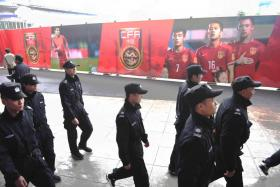 Security guards marching outside the Helong Stadium in Changsha, Hunan, where China host South Korea in tonight's politically charged World Cup qualifier.