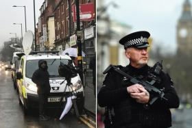 West Midlands police vehicles and journalists ouside a property in Hagley Road, Birmingham, central England, 23 March 2017.  An armed policeman guards a locked down Whitehall in central London.