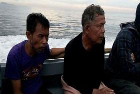 A handout photo made available by the Western Mindanao Command (WestMinCom) of the Armed Forces of the Philippines shows rescued Malaysians Tayudin Anjut (L) and Abdurahim Bin Sumas (R) on a boat after being rescued by the Philippine military in Sulu prov