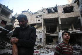 An injured man stands with his son in front of thier destroyed house in Douma, Syria