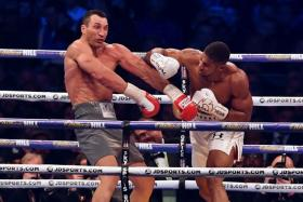 Britain's Anthony Joshua (R) throws a punch at Ukraine's Wladimir Klitschko during the fourth round of their IBF, IBO and WBA, world Heavyweight title fight