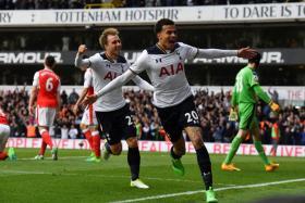 Dele Alli (R) celebrates scoring the opening goal with Tottenham Hotspur's Danish midfielder Christian Eriksen