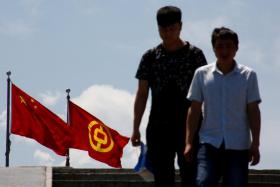 People walking past the national flag of China and a flag of the Bank of China in Beijing.
