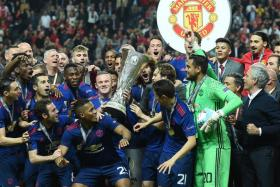 Manchester United's Portuguese manager Jose Mourinho and players pose with the trophy after during the UEFA Europa League final football match Ajax Amsterdam v Manchester United on May 24, 2017 at the Friends Arena in Solna outside Stockholm