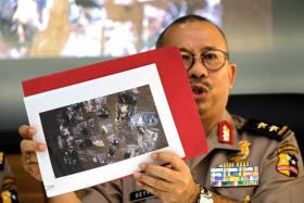 Indonesian National Police spokesperson Setyo Wasisto shows a picture of evidence collected from Kampung Melayu bomb blast site at police headquarters in Jakarta.