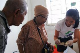 Mr Abdul Wahab Sarman (left) and his wife (centre) sorting through their belongings with a Habitat for Humanity volunteer (right).