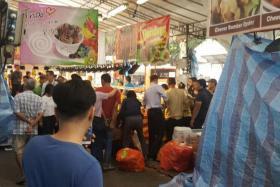Workers being arrested at the Hari Raya bazaar in Geylang Serai.