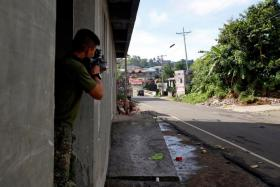 A Philippine Marine fires a weapon towards the stronghold of Maute group in Marawi.