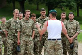 Members of the England national football team are briefed by a British Royal Marine at the Commando Training Centre Royal Marines in Exmouth, Devon.