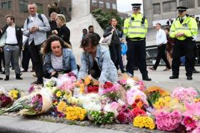People lay flowers at a police cordon on the south side of London bridge, near to Borough Market in London on June 5, 2017, in tribute to the victims of the June 3 attacks.