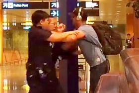 A screenshot from one of two videos showing a man, believed to be the accused, tussling with police at Changi Airport in April 2017. It emerged that Australian Jason Peter Darragh had likely broken the law on multiple occasions during several drunken sprees in Singapore here, with a total of 11 charges levelled against him.