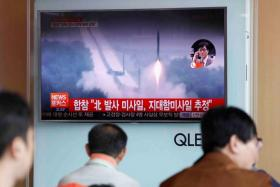 People watch a TV broadcast of a news report on North Korea firing what appeared to be several land-to-ship missiles off its east coast, at a railway station in Seoul, South Korea,