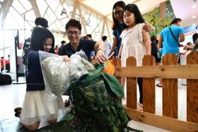 A father helps his daughter pack items into a field pack at the Safra Jurong open house yesterday.