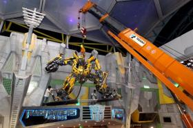 File photo of workers installing a model of Bumblebee at Transformers: The Ride in Universal Studios Singapore in 2011. A former Resorts World Sentosa director who oversaw the construction and installation of the attraction was jailed for corruptly taking bribe payments from a subcontractor.