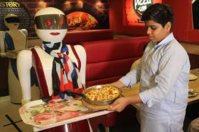 A young customer picking up a pizza from a tray carried by a robot waitress at a pizza restaurant in Multan.