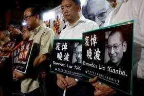 Pro-democracy activists mourn the death of Chinese Nobel Peace laureate Liu Xiaobo, outside China's Liaison Office in Hong Kong.