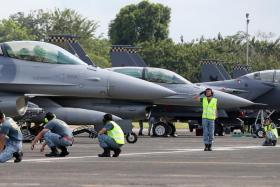A ground marshall saluting the pilot of an F-16 as he prepares to take off from Tengah Air Base.
