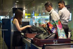Customs officers inspect a traveller's hand luggage at Changi Airport.