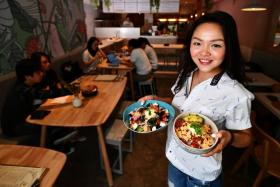 Ms Lee Li Ping, founder of Sogurt, with flagship outlet Kara Cafe & Dessert Bar's Coco Cashew Pomelo Quinoa bowl and Taco Mexx Chicken Grain bowl.