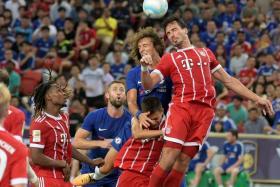 Bayern Munich's Mats Hummels wins a header against Chelsea's David Luiz during their ICC match at the National Stadium.
