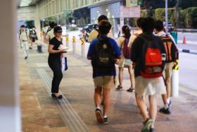 A woman giving out fliers promoting a tuition centre outside Hwa Chong Institution's gate near Tan Kah Kee MRT station on 26 July 2017.