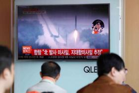 People watching a TV broadcast of a news report on North Korea firing what appeared to be several land-to-ship missiles off its east coast.