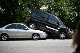 The impact from the initial collision pushed the black van onto the silver car