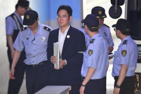 Vice-chairman of Samsung Electronics, is escorted by prison guards as he arrives at the Seoul Central District Court in Seoul on August 2, 2017