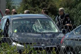 French police  surround a BMW car with several bullet impact marks.  The man suspected of ramming a car into a group of soldiers in a Paris suburb, was shot and arrested on the A16 motorway, near Marqui.