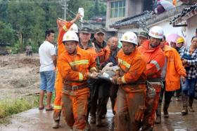 Chinese paramilitary police and rescue workers carrying survivors after an earthquake in Jiuzhaigou, Sichuan province.